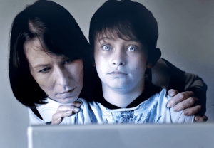 child on computer with mother watching